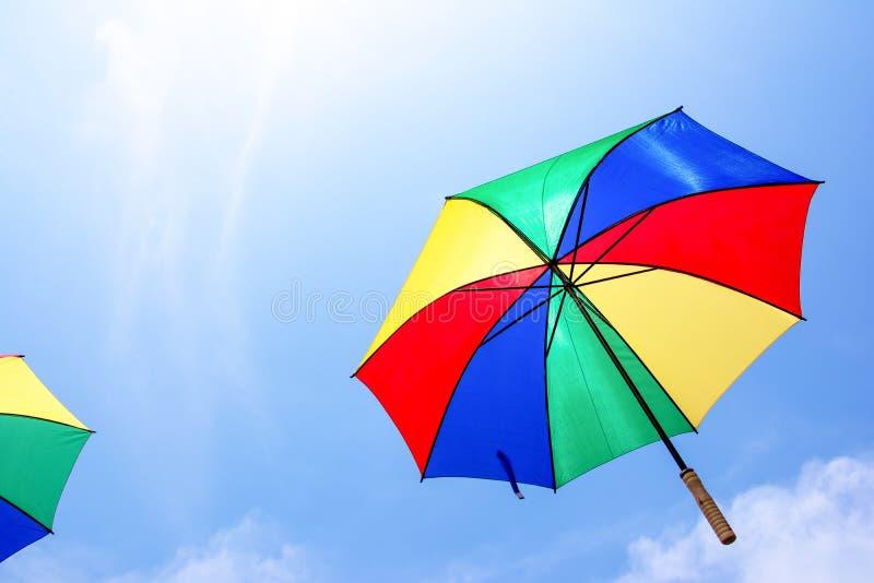 Paraguas colorido que flota debajo del cielo hermoso foto de archivo