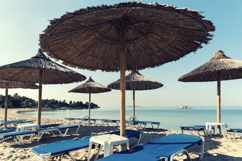 Paraguas de la paja en una playa en bahía hermosa y ningunas personas en Grecia imagen de archivo libre de regalías