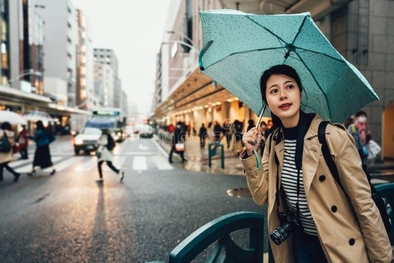 Paraguas de la tenencia del fotógrafo que camina la ciudad ocupada imagen de archivo libre de regalías