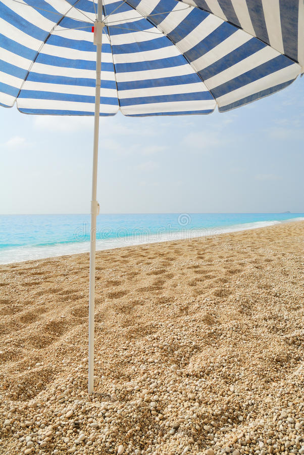 Paraguas de Sun pegado en un Pebble Beach fotografía de archivo libre de regalías