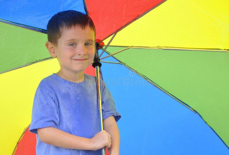Paraguas del arco iris de la explotación agrícola del muchacho fotografía de archivo