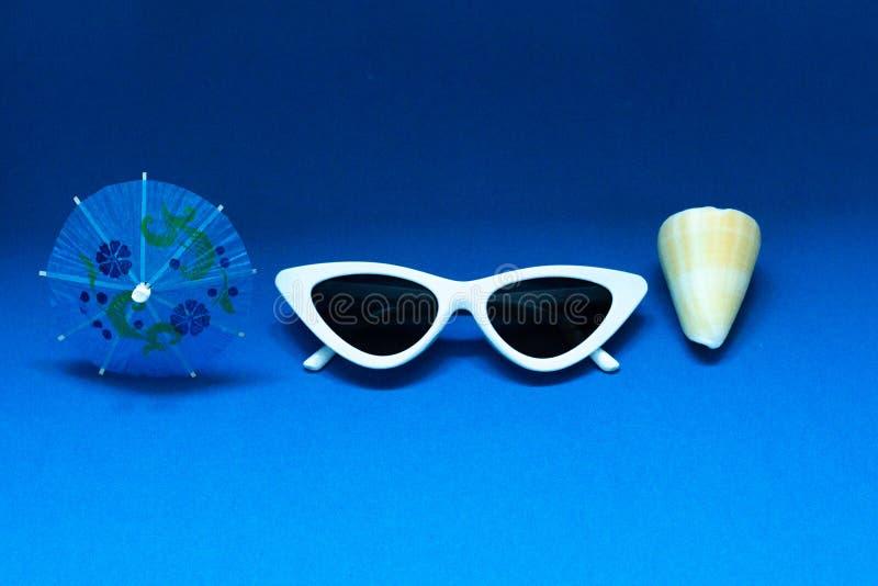 Paraguas del cóctel, gafas de sol blancas stilish y una cáscara en un fondo azul brillante El concepto de vacaciones del mar del  fotografía de archivo