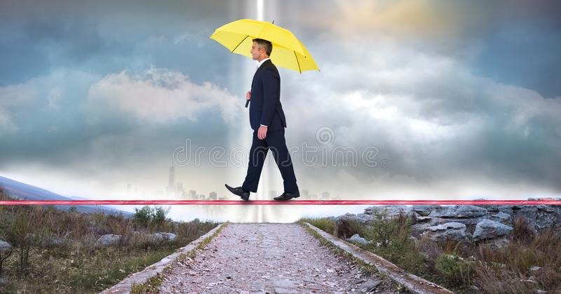 Paraguas que lleva del hombre de negocios mientras que camina en cuerda imagenes de archivo