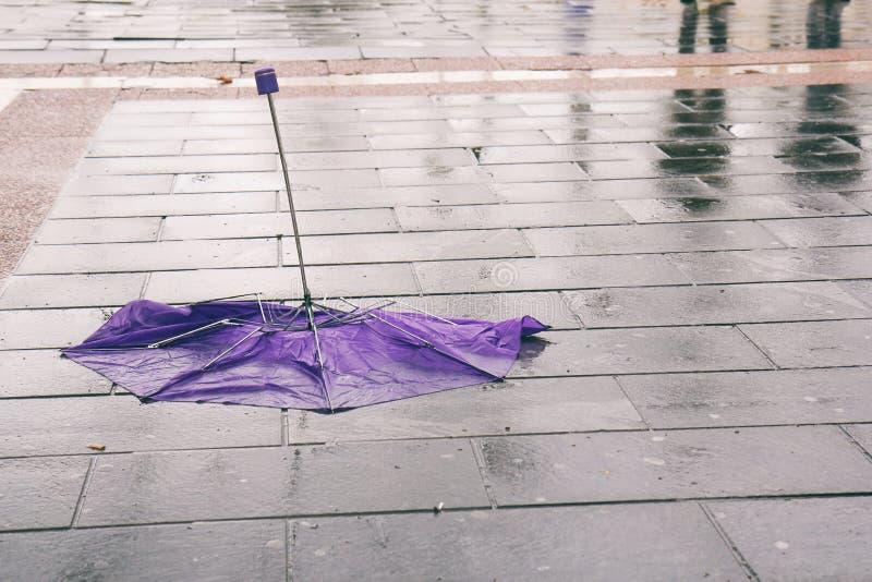 Paraguas quebrado en la acera mojada imagen de archivo
