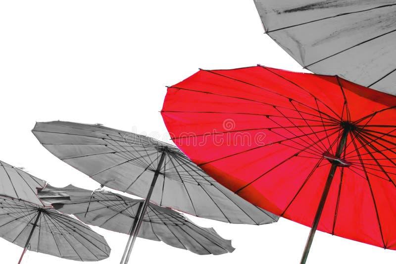 Paraguas rojo único en el grupo de paraguas pálidos, concepto de único, siendo diferente, en el fondo blanco fotos de archivo libres de regalías