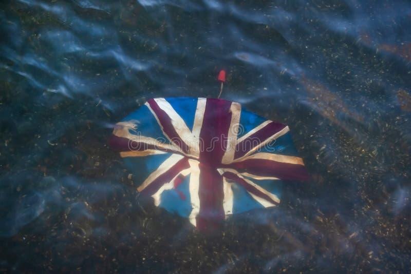 Paraguas roto con Union Jack en él, desechado en el río bajo foto de archivo