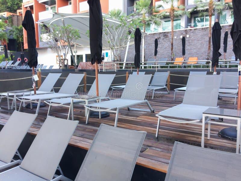 Paraguas y silla de lujo hermosos alrededor de la piscina al aire libre foto de archivo libre de regalías
