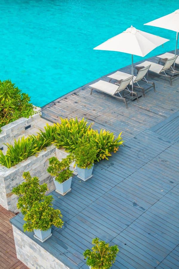 Paraguas y silla de lujo hermosos alrededor de la piscina en hote imagen de archivo libre de regalías