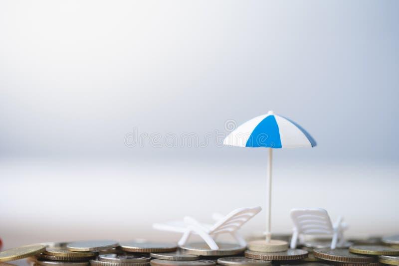 Paraguas y silla en pila de las monedas fotos de archivo libres de regalías