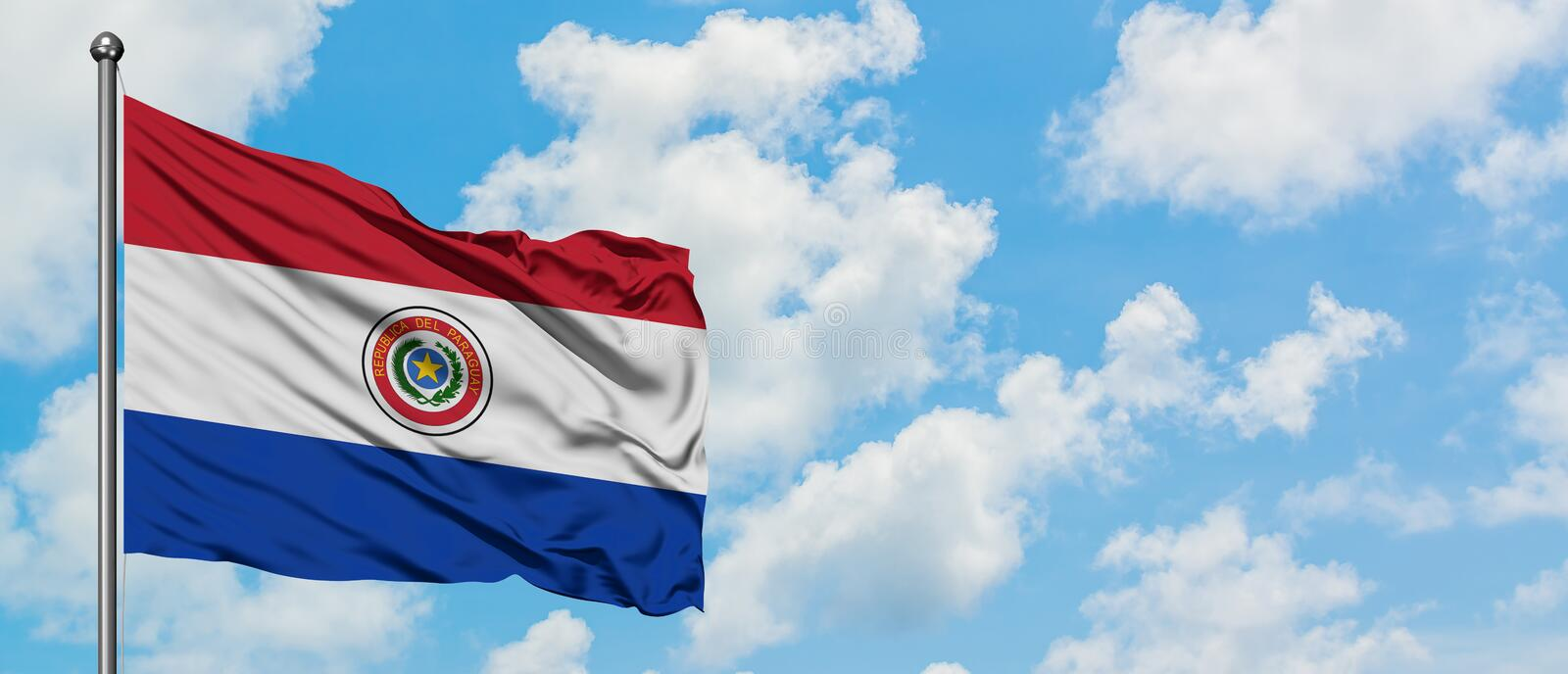 Paraguay flag waving in the wind against white cloudy blue sky. Diplomacy concept, international relations.  stock image