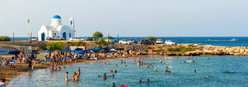 PARALIMNI CYPERN - 17 AUGUSTI 2014: Fullsatt strand med turister fotografering för bildbyråer