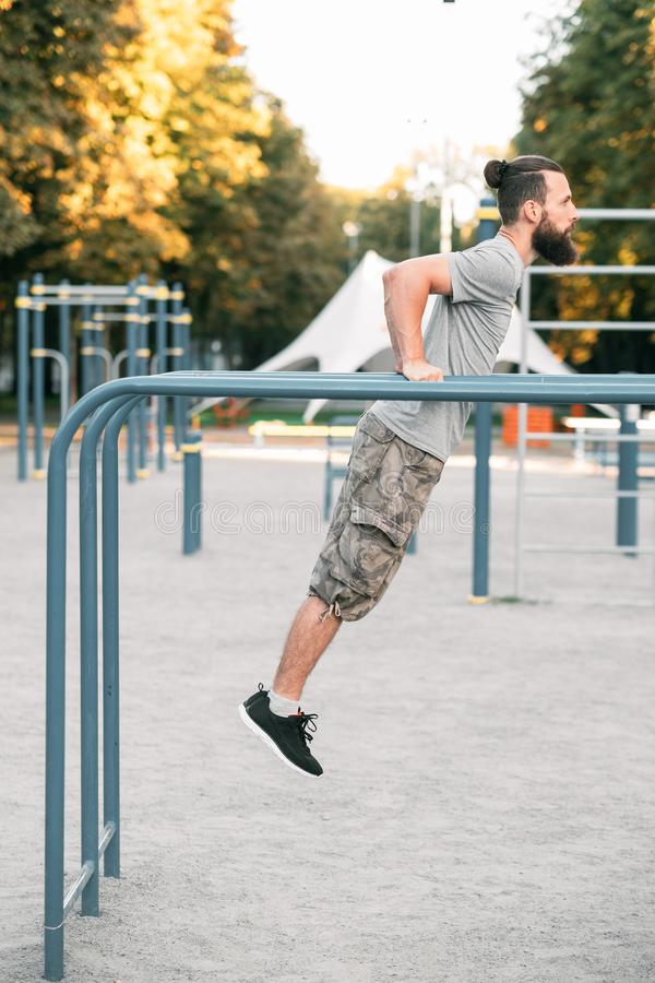 Parallel bar dips strength workout sport lifestyle. Parallel bar dips. strength power and workout. sport lifestyle. man exercising outdoors royalty free stock photography