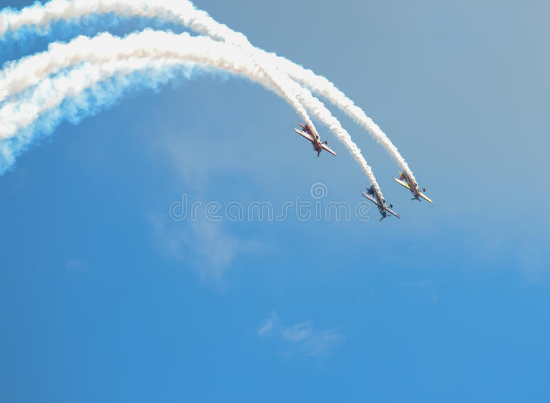 Parallel Diving Stunt Planes. Three stunt planes make a synchronized looping dive while trailing smoke at an air show demonstration royalty free stock photography