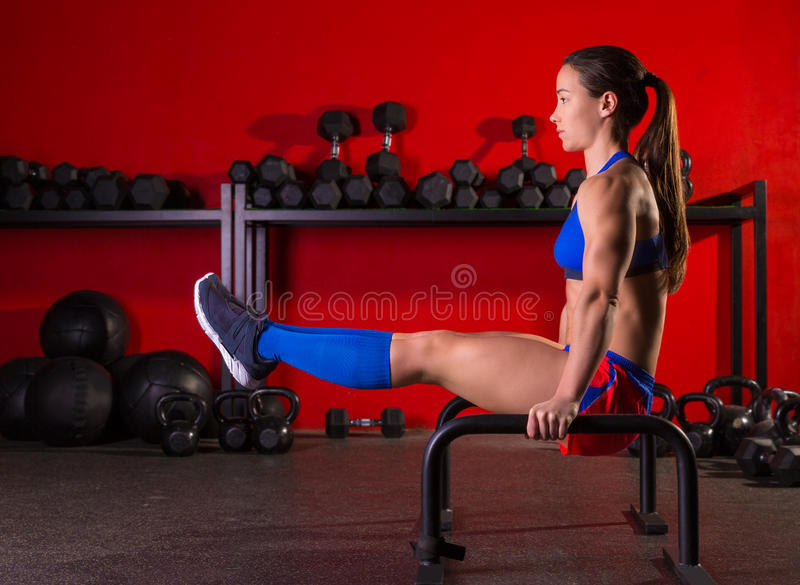 Parallettes woman parallel bars workout at gym. Parallettes woman parallel bars workout exercise at red gym stock image