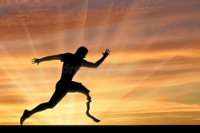 Paralympic-Läufer mit Prothesenüberfahrt-Zielliniesonnenuntergang lizenzfreie stockfotos