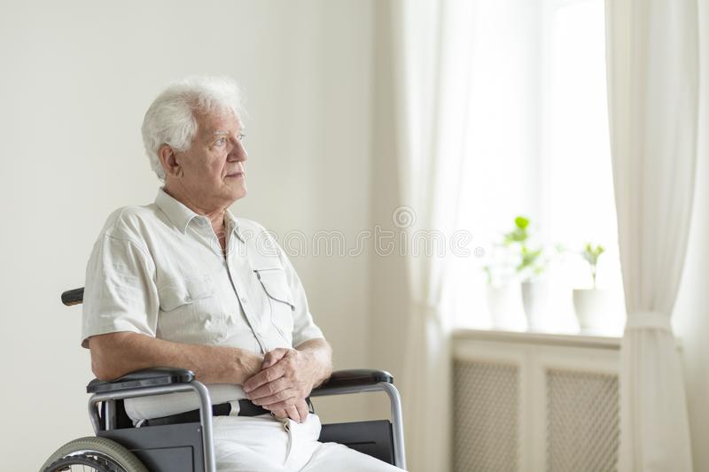 Paralyzed, elderly man in a wheelchair alone in a room royalty free stock photo