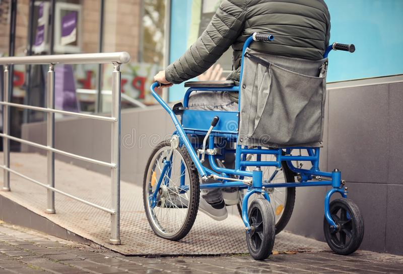Paralyzed man in wheelchair on ramp royalty free stock photography