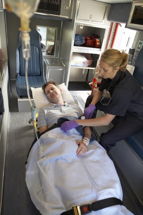 Paramédico con el paciente en ambulancia fotografía de archivo libre de regalías