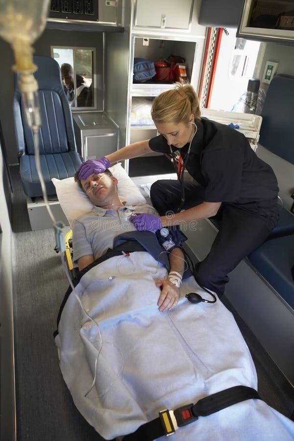 Paramédico con el paciente en ambulancia fotos de archivo libres de regalías