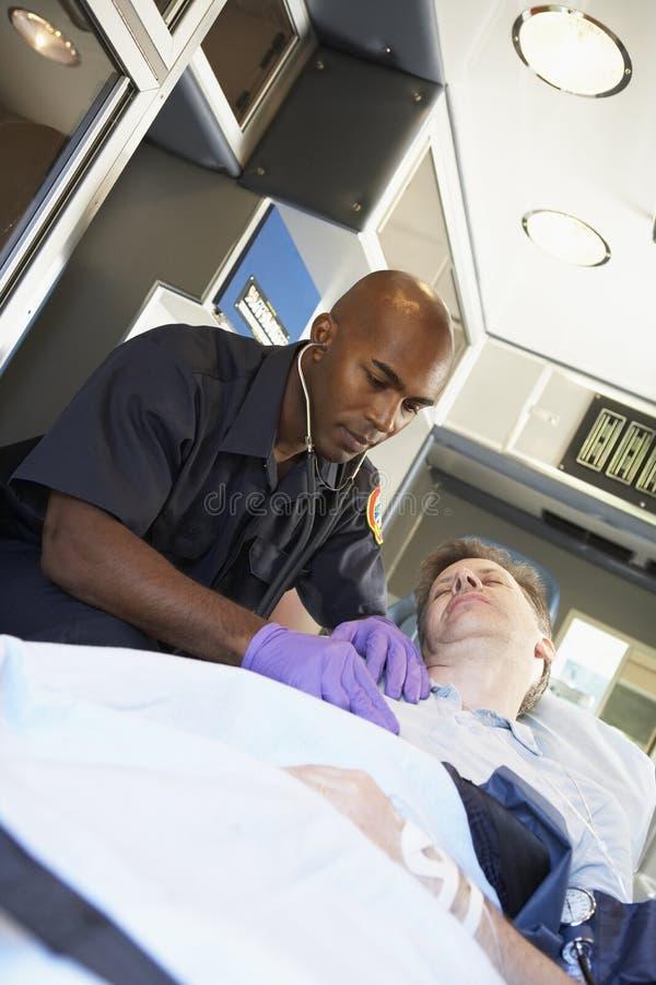 Paramédico que atiende al paciente en ambulancia imagen de archivo