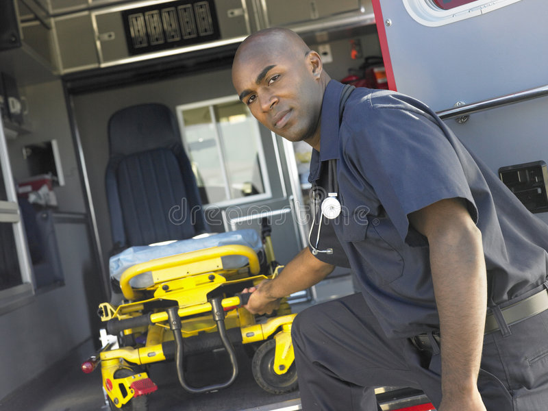 Paramédico que quita la camilla de la ambulancia fotografía de archivo