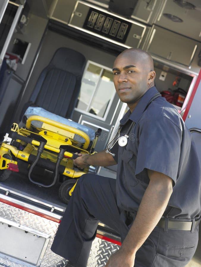 Paramédico que quita la camilla de la ambulancia imagenes de archivo
