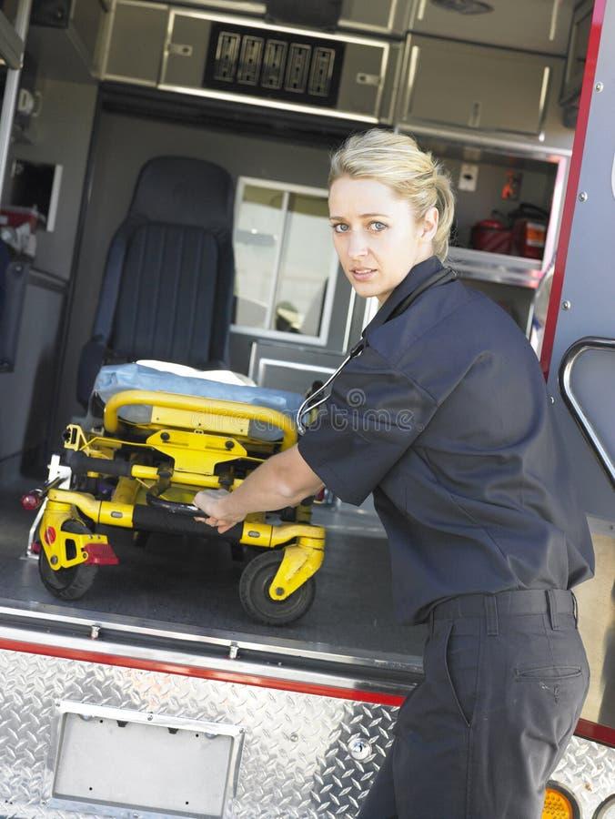 Paramédico que quita la camilla de la ambulancia foto de archivo