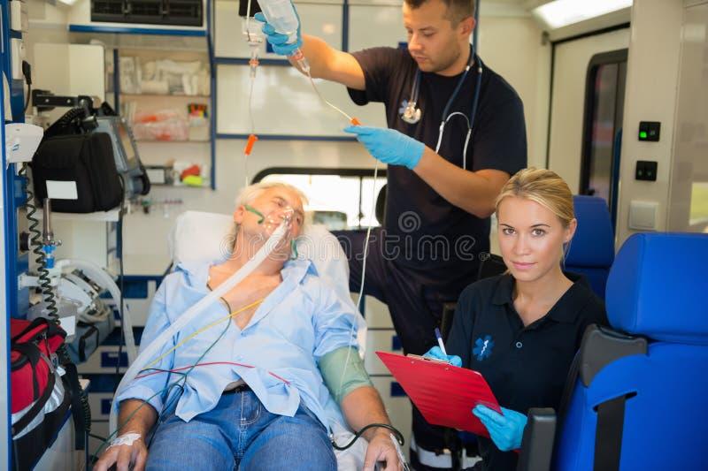 Paramédico que trata al paciente herido en ambulancia fotos de archivo