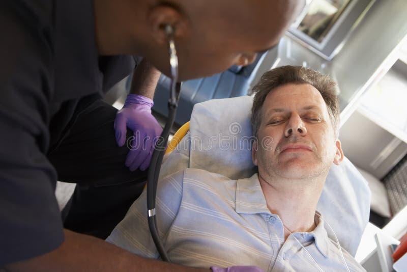 Paramédico que usa el estetoscopio en paciente foto de archivo