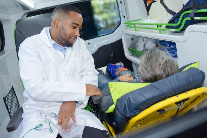 Paramédico sentado com o paciente na ambulância traseira imagens de stock royalty free