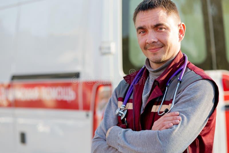 Paramédico sonriente en fondo de la máquina de la ambulancia fotos de archivo libres de regalías