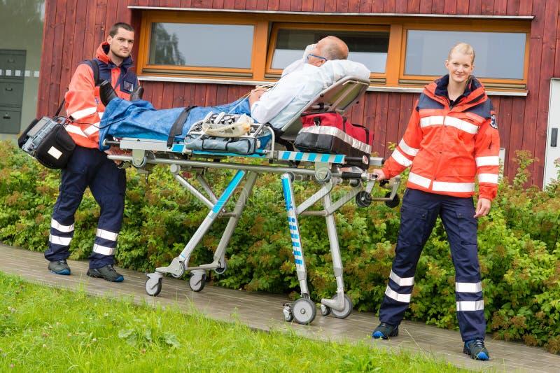 Paramédicos com o paciente no dae (dispositivo automático de entrada) da ambulância do esticador fotos de stock royalty free