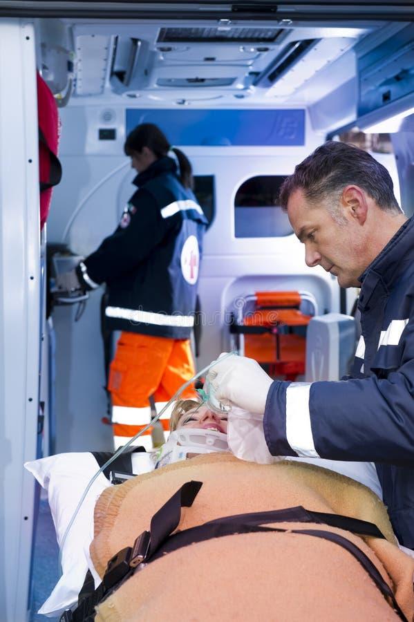 Paramédicos con el paciente foto de archivo