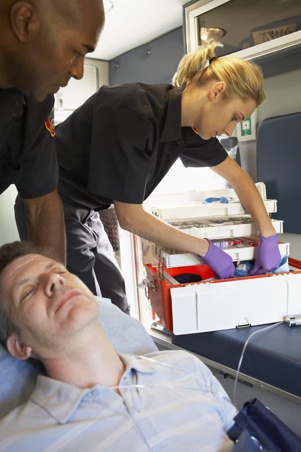 Paramédicos con el paciente en ambulancia imágenes de archivo libres de regalías