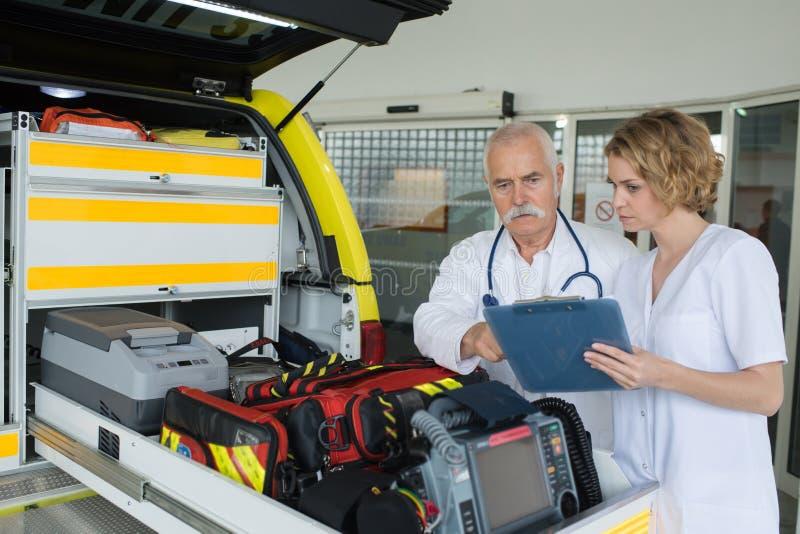 Paramédicos da equipe que verificam a engrenagem na ambulância fotografia de stock royalty free