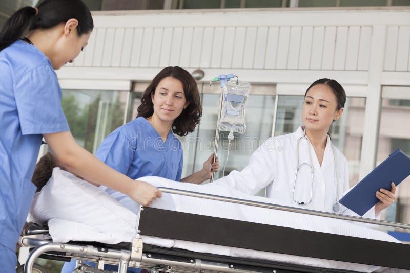 Paramédicos de sexo femenino y doctor que ruedan en un paciente en un ensanchador delante del hospital imágenes de archivo libres de regalías