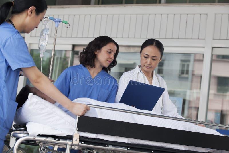 Paramédicos e doutor que examinam para baixo o informe médico do paciente em uma maca na frente do hospital foto de stock