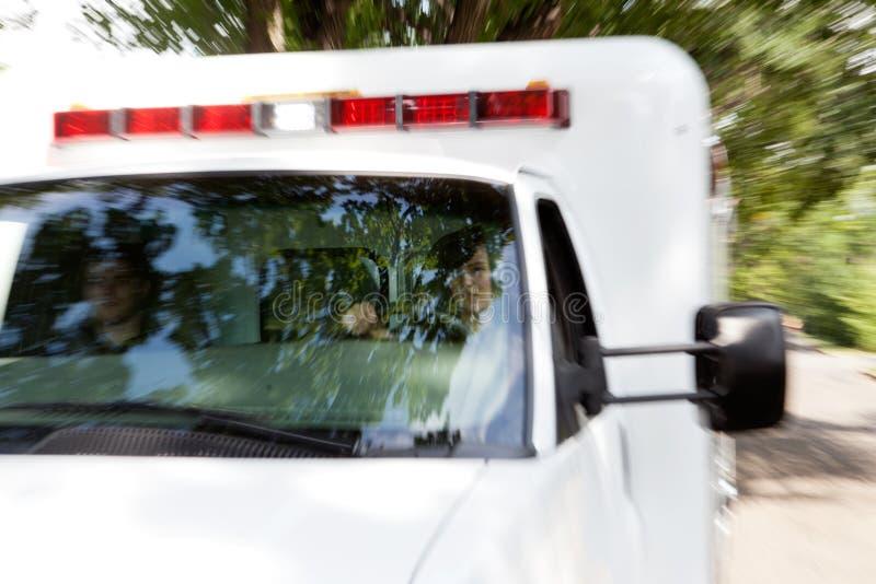 Paramédicos en ambulancia que apresura foto de archivo