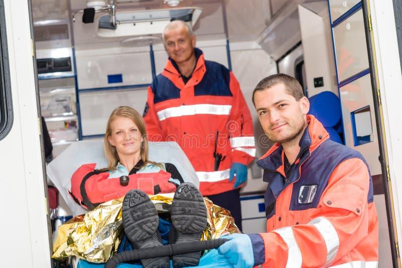 Paramédicos que ayudan a la mujer en ensanchador en ambulancia fotografía de archivo