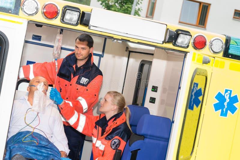 Paramédicos que controlan al paciente del goteo IV en ambulancia imagen de archivo