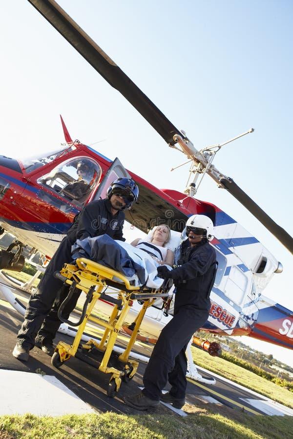Paramédicos que descargan al paciente del helicóptero foto de archivo libre de regalías