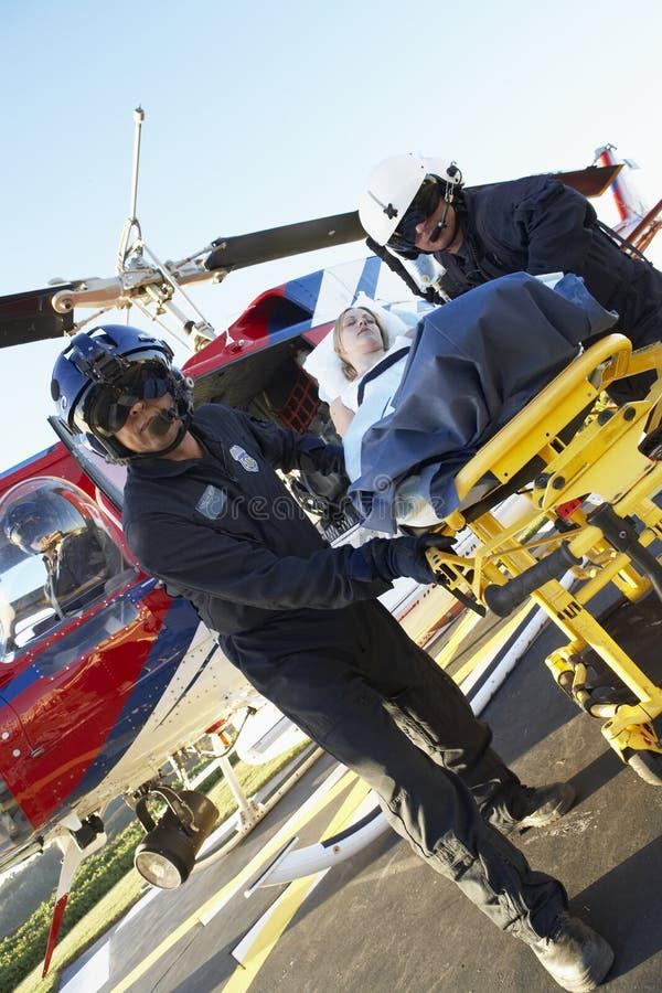 Paramédicos que descargan al paciente del helicóptero fotos de archivo libres de regalías