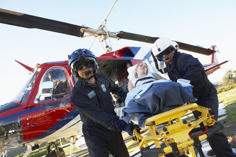 Paramédicos que descargan al paciente del helicóptero imagen de archivo
