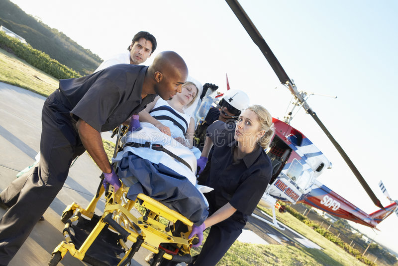 Paramédicos que descargan al paciente del helicóptero fotografía de archivo