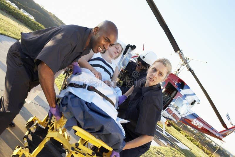 Paramédicos que descargan al paciente del helicóptero fotos de archivo
