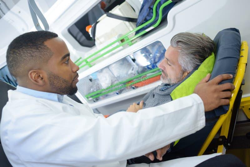 Paramédicos que hablan con el paciente fotografía de archivo libre de regalías