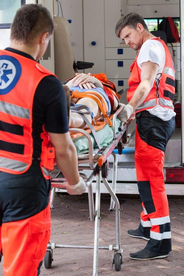 Paramédicos que llevan a la muchacha inconsciente al hospital fotografía de archivo libre de regalías