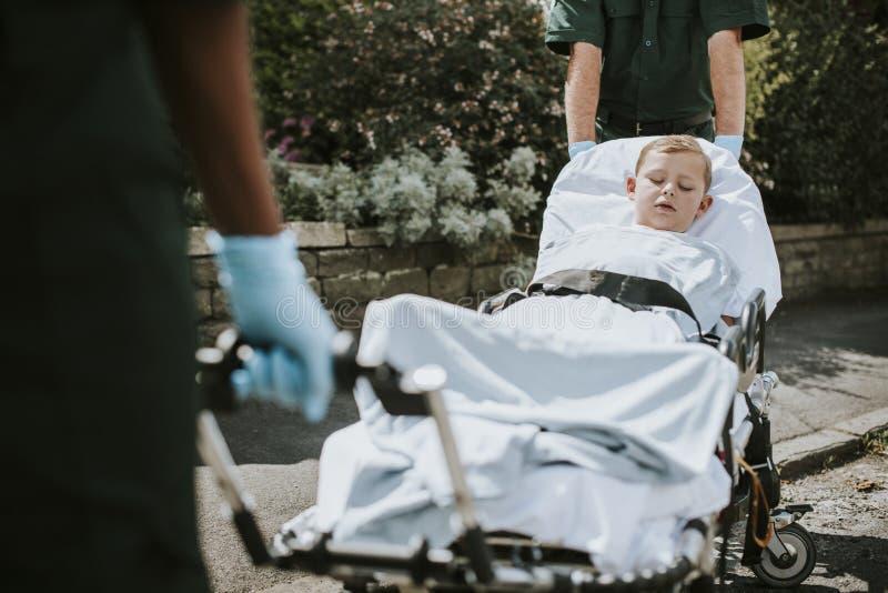 Paramédicos que mueven a un paciente joven en un ensanchador a una ambulancia fotografía de archivo