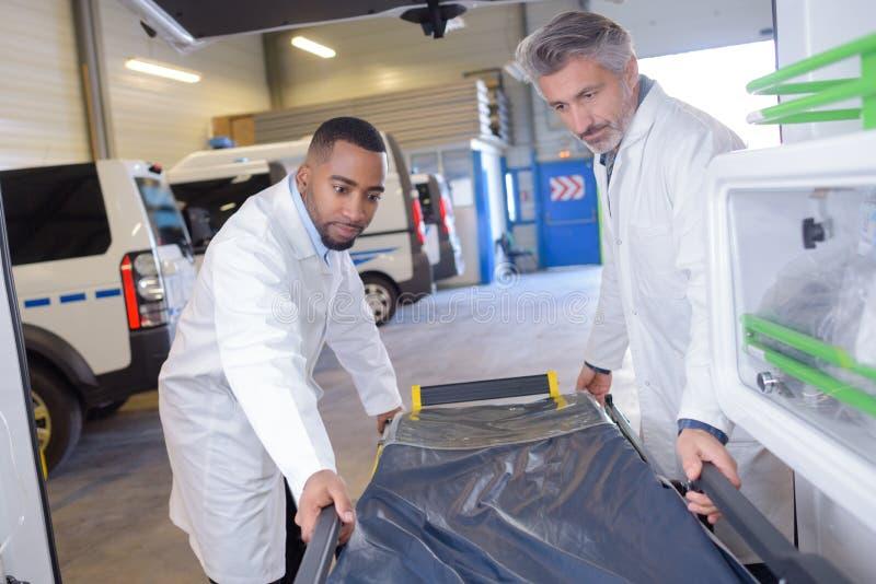Paramédicos que põem a maca de novo na ambulância imagens de stock royalty free