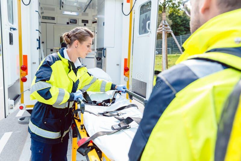 Paramédicos que preparam a maca na ambulância fotos de stock